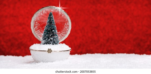 vintage glass bauble and small Christmas tree in snow red background. Merry Christmas and Happy New Year seasons greetings card. Crystal and golden elegant retro style decoration