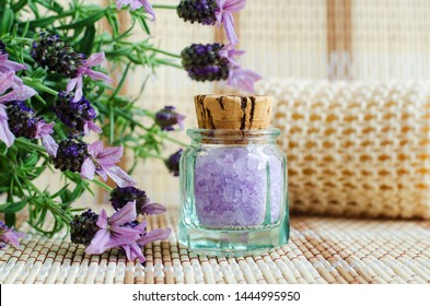 Vintage glass bottle with aroma lavender bath salt (foot soak). Topped lavender flowers close up. Natural skin care. DIY beauty treatments and spa concept. Copy space.