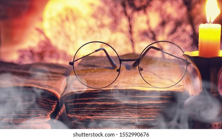Vintage glasses on an old retro book on a background of the moon. Reading book by candlelight. The concept of book thrillers and novels.