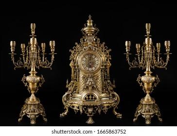 vintage gold watch with candelabra on black background, bronze clock and candelabra, gold candlesticks and clock, antique clock and candlesticks, vintage clock with chandeliers on a black background