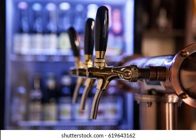 Lot of vintage Golden beer taps in a bar with a fridge of bottles in the background