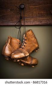 Vintage golden football boots hanging on a locker room