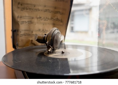 The vintage gramophone playing the music from the old vynil record