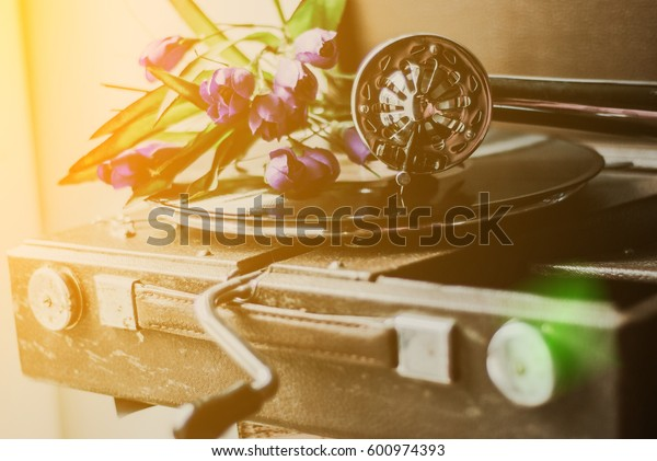 Vintage gramophone with a vinyl and flowers