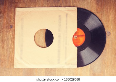 Vintage gramophone vinyl record in an envelope on wooden background