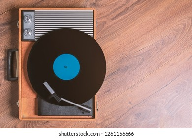 Vintage Gramophone with a vinyl record on wooden table, top view and copy space,photo.