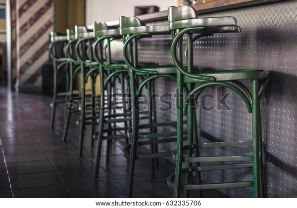 Vintage green bar stools stand in a row next to the bar counter