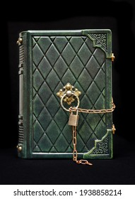 Vintage green leather book with chain and padlock stay up isolated over black background