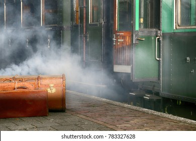 Vintage green railway coach with doors opened at a railway station with vintage suitcases waiting to be boarded. Steam coming from under the coach.