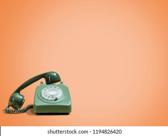 Vintage green rotary phone on a retro orange background with handset off and space for copy and text