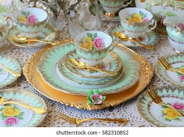 vintage green tea cup set with pink and yellow roses on a gold charger plate, wedding