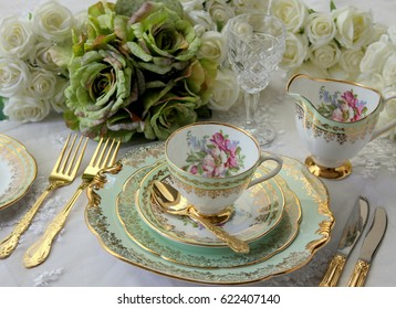 Vintage green teacup, saucer and plate with gold cutlery flatware and roses on a lace table cloth - wedding tea party