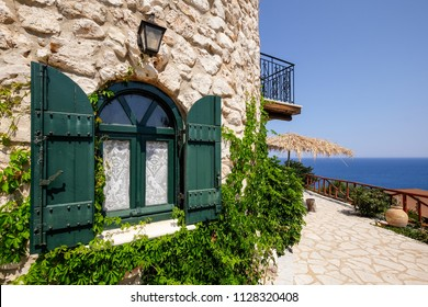 Vintage green window on a brick house with ocean background, Zakynthos, Greece