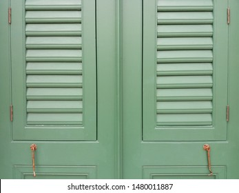 Vintage green wooden louver windows and wooden frame with wooden wall background. Ventilation and lighting design concept.