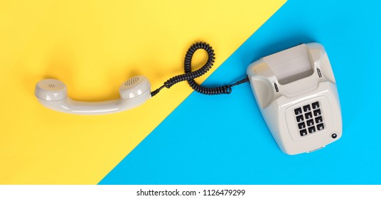 Vintage grey telephone with a colorful background