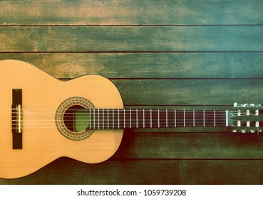 Vintage Guitar on the Wooden Background
