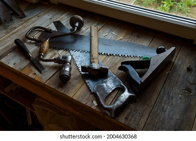 Vintage hacksaw, jointer, chisel, hammer and drill are on workbench in workshop