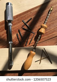Vintage hand push and Archimedes drills and bits over maple and sapele boards.