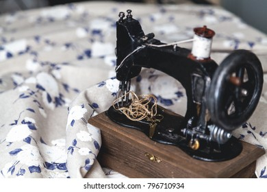 Vintage hand sewing machine and a skein of threads on a white cloth background with a blue closeup pattern.