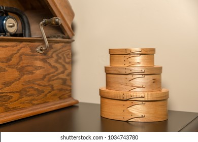Vintage hand-crafted shaker boxes next to antique cylindrical phonograph.  Selective focus on the boxes.