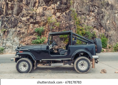 Vintage handmade 4x4 off road truck vehicle at the beautiful mountain road. Offroad adventure tour vacation concept. Side view. Car expedition wallpaper. Shallow focus.