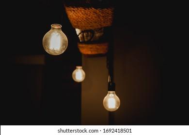 Vintage hanging Edison light bulb over dark background. lighting decoration. retro luxury light lamp decor glowing.