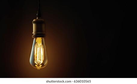 Vintage hanging Edison light bulb over dark background