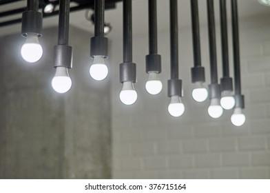 vintage hanging energy light bulbs on stone wall retro, background