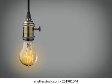 Vintage hanging light bulb over gray background