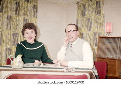 Vintage happy 1950´s couple smiling at camera in a retro decor.