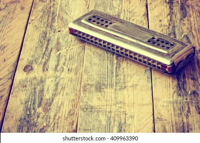 vintage harmonica lying on wooden table, retro toned effect