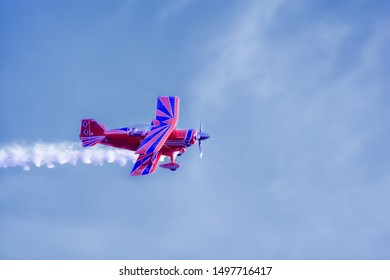 Vintage helical red and blue biplane in flight at an air show