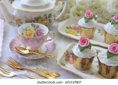Vintage high tea party - pink teacups and teapot with yellow and pink roses and cup cakes