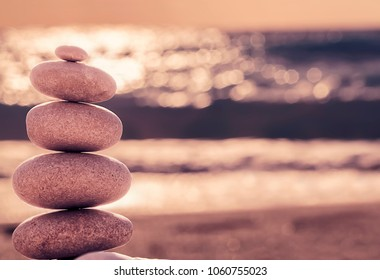 Vintage hipster style Zen meditation background, balanced stones stack on sea beach