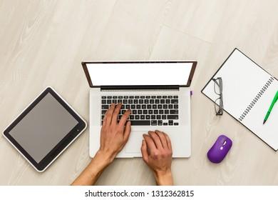 Vintage hipster wooden desktop top view, male hands using a laptop