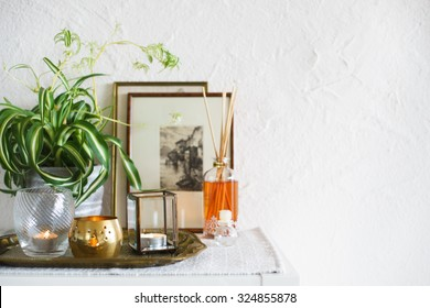 Vintage home decor: candles, aroma diffuser, plant and frames. Selective focus