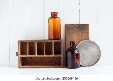 Vintage home decor: old wooden boxes and vintage brown glass bottles on white wooden board, retro home interior.