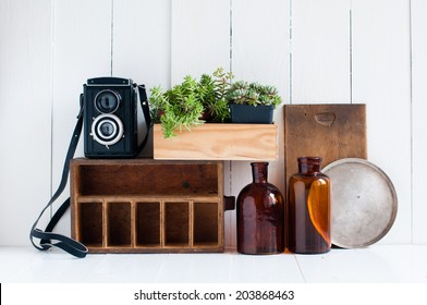 Vintage home decor: old wooden boxes, houseplants, camera and old brown glass bottles on white wooden board, retro home interior.