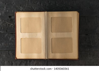 Vintage home photo album open on dark wooden table. The subject of family values. The view from the top. Flat lay.