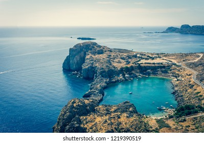 Vintage horizontal photo with nice cove on Rhodes island. Cove is captured from ancient acropolis above the Lindos town. Several sunbeds are visible in the cove hidden by rocks.