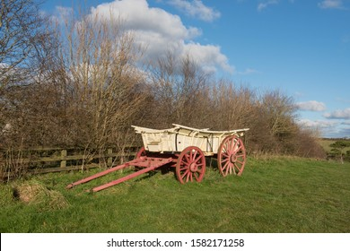Vintage Horse Drawn Cart by a Fence in a Field with a Bright Cloudy Blue Sky Background