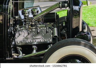 Vintage hot rod with exposed flathead engine and wide whitewall tire