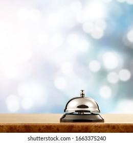 Vintage hotel reception service bell on the desk.