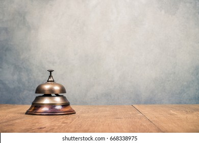 Vintage hotel reception service desk bell front textured concrete wall background. Old retro style filtered photo