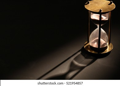 Vintage hourglass on dark background with long shadow