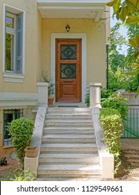 vintage house entrance with marble stairs and solid wooden door