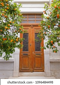 vintage house entrance wooden door and orange trees, Athens Greece