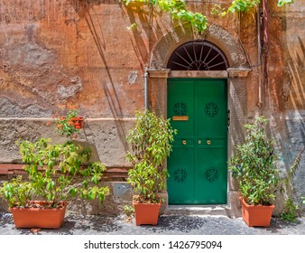 vintage house exterior with green entrance arched door on ocher wall and flower pots, Trastevere old district, Rome Italy