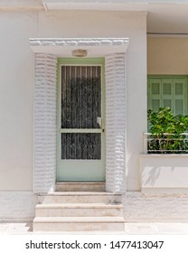 vintage house pale white facade with light green door and window, Athens Greece