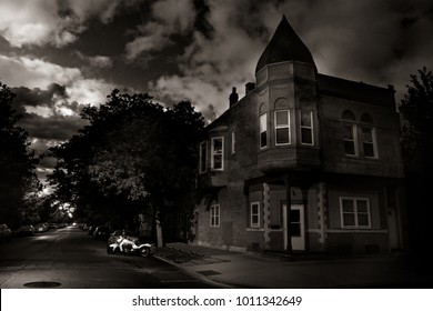 A vintage house with a tower looking like a castle during a cloudy and stormy night in black and white.
